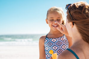 Mother applying sunscreen to nose of young daughter