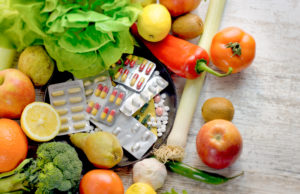 Picture of supplements with fruits and vegetables surrounding them