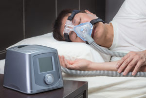 Asian man with sleep apnea using CPAP machine and wearing headgear mask connected to air tube