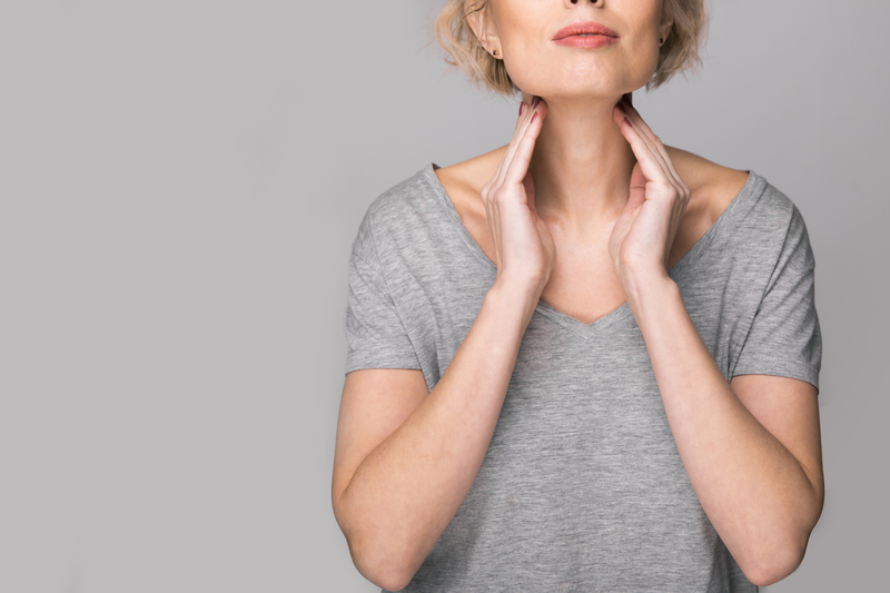 Female checking her thyroid gland with her hands