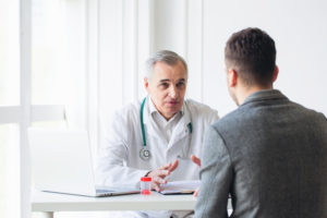 Older doctor consults younger man in doctor office