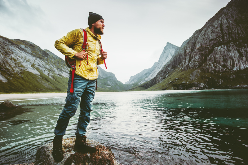 Man backpacking next to a lake and mountains