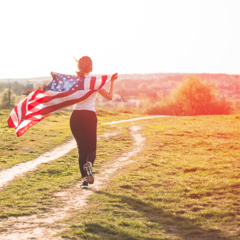 Happy woman running on a trail holding an American flag