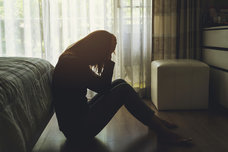Depressed woman sitting on floor in bedroom with her head in her hands