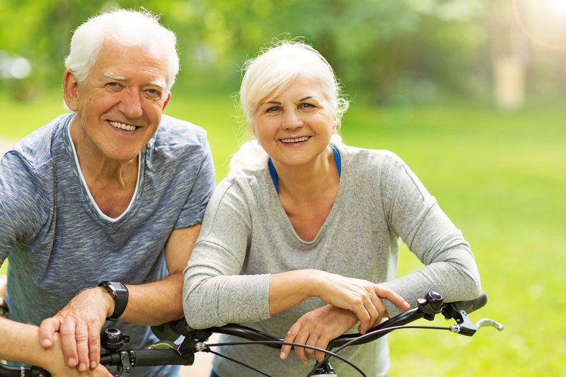 Older man and woman smiling while sitting on their bikes outside.
