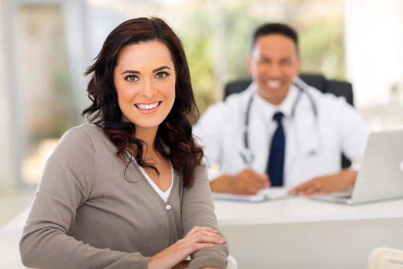 Woman smiling in doctor's office in front of doctor's desk where a male doctor is sitting.