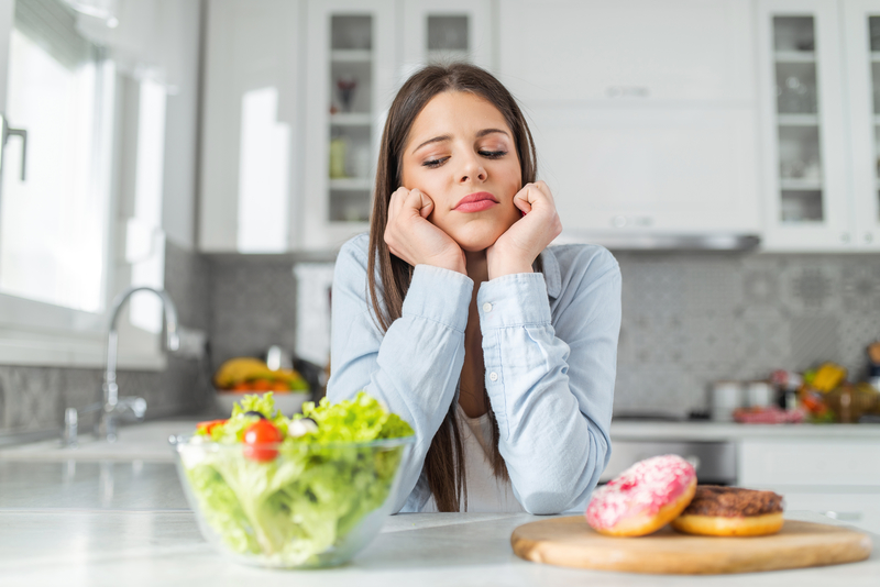 Young woman looking at a bowl of salad and a plate of donuts.