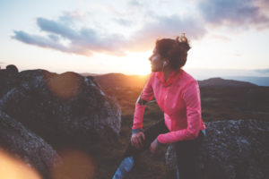 Woman resting while she jogs on a mountain side during sunset.