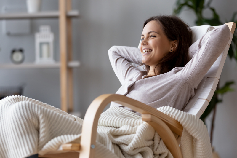 Woman sitting in a rocking chair with her arms behind her head and smiling.