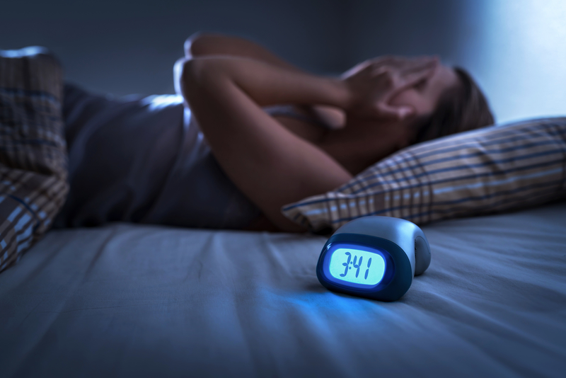 Woman laying in bed in the middle of the night with her hands over her face because she can't sleep.