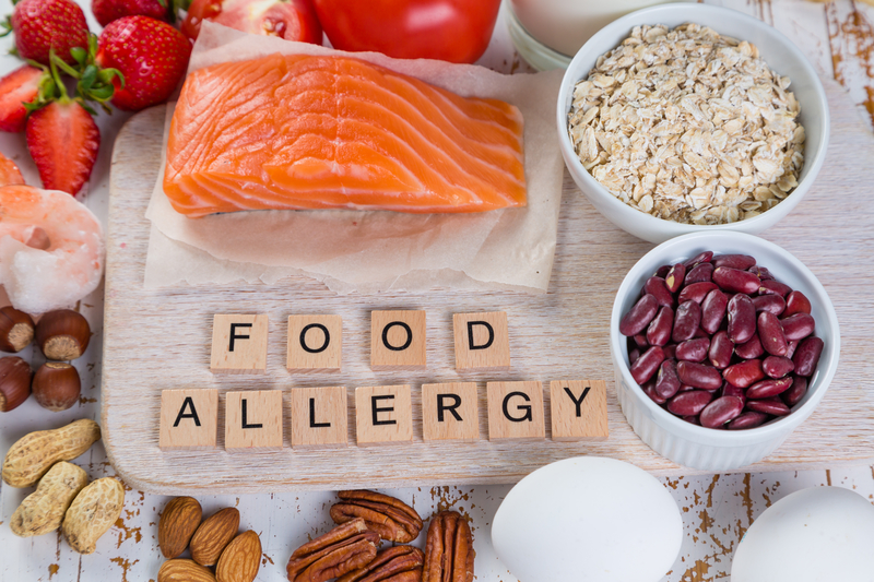 """Picture of healthy food (fish, nuts, grains, beans, etc.) spaced around tiles that spell out """"food allergy""""."""