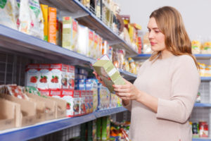 Woman shopping for food and looking at the ingredient list on a box of food.