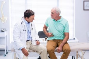 Older patient sitting with doctor on a medical table while holding his side.