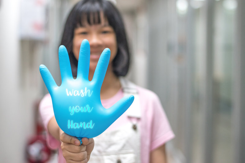 """Young child smiling while holding a blue balloon that says """"wash your hand."""""""