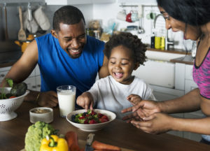 African American family sitting together at the dinner table while eating healthy food.
