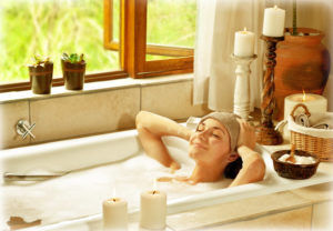 A woman laying in a bubble bath and relaxing with candles nearby.